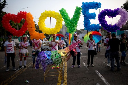 "Revelers hold balloons, representing the colors of a rainbow, to form the word, ""Love"" during the annual gay pride parade in Lima, Peru, Saturday, June 27, 2015. (AP Photo/Rodrigo Abd) ORG XMIT: ABD107"